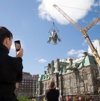 The Laurier Tower at the West Block on Parliament Hill is removed with the aid of a crane as reconstruction continues. A former staffer to a Conservative Senator has been charged with fraud and breach of trust in connection to the West Block's renovations.